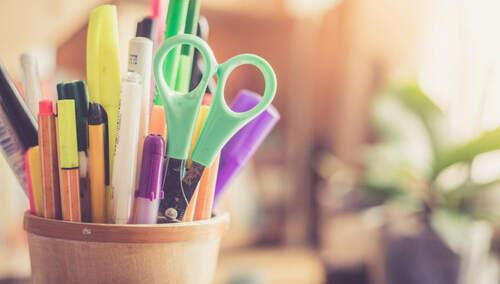 Cubilete en mesa de oficina con tijeras